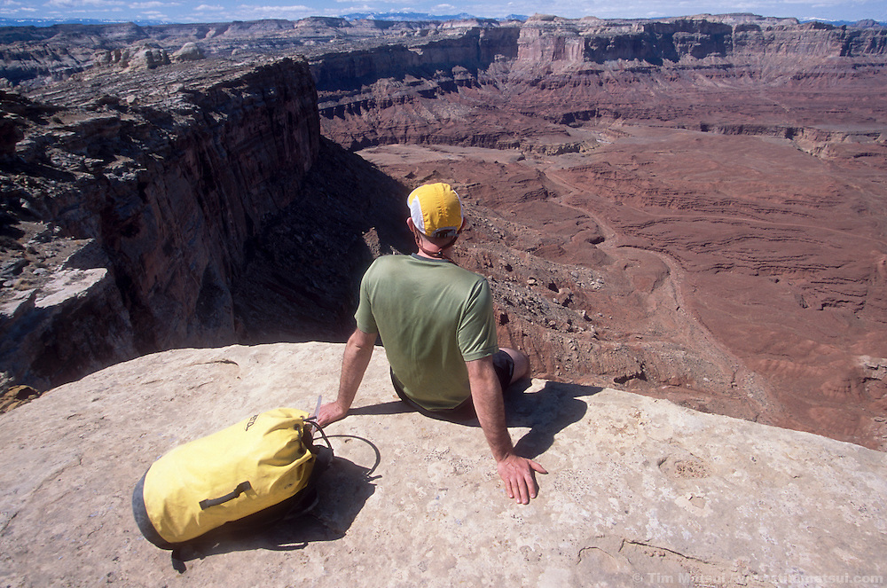 Jeff Friesen enjoys the view on the approach to Miner's Hollow (Knotted Rope Canyon) in the San Rafael Swell, Utah. Below are the canyons of the Muddy Creek drainage and the faint line of the dirt road to the old Hidden Splendor uranium mine.