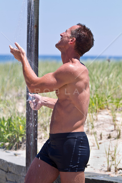 man in an outdoor shower by the ocean in East Hampton, NY