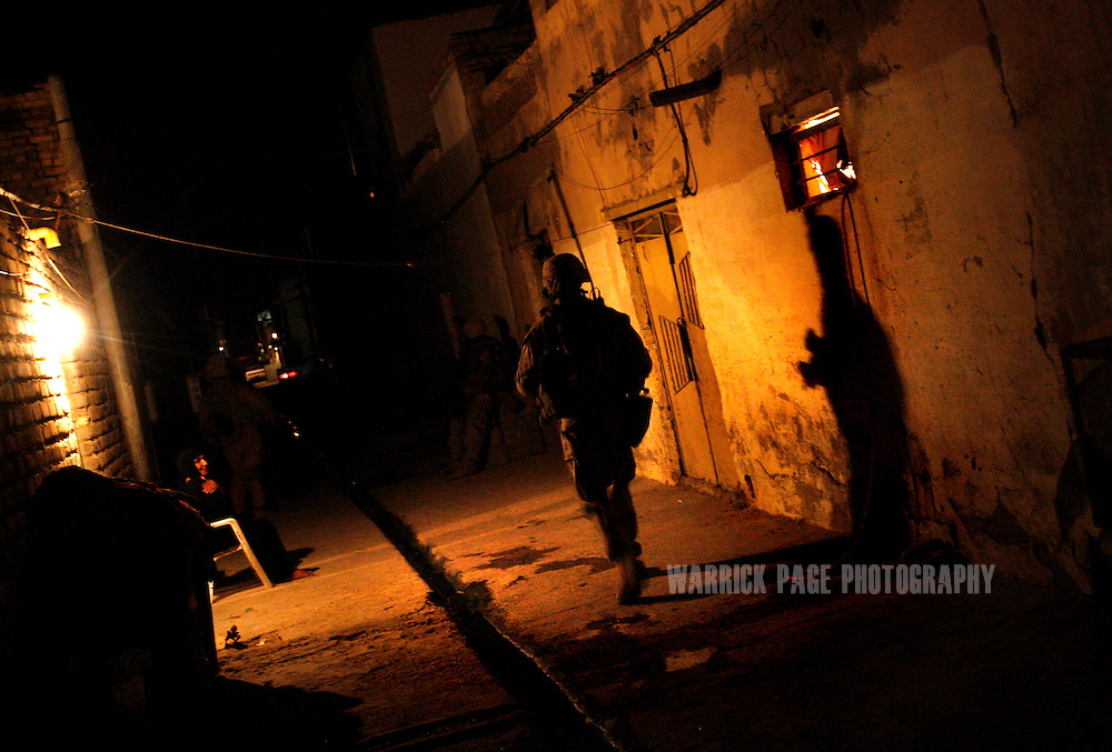 IRAQ, BASRA - JULY 4: A US Marine of 1st Battalion 26th Brigade 2nd Division, patrols the alleyways of the poverty stricken neighborhood of Hayaniyah, July 4, 2008 in Basra, Iraq. When British forces withdrew in 2007, Basra deteriorated into street battles between numerous Shiite militias and criminal gangs. In April 2008, Iraqi prime minister, Nouri al Maliki, sent two Iraqi army divisions to retake control of Basra. While the fighting has ended, unemployment is rife, at about 70 per cent. Since early 2008, Iraq's security situation has improved with oil production increasing, record government surplus and easing sectarian tensions. (Photo by Warrick Page)
