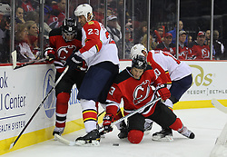 Feb 11; Newark, NJ, USA; New Jersey Devils right wing David Clarkson (23) plays the puck from his knees while being defended by Florida Panthers defenseman Tyson Strachan (23) during the second period at the Prudential Center.