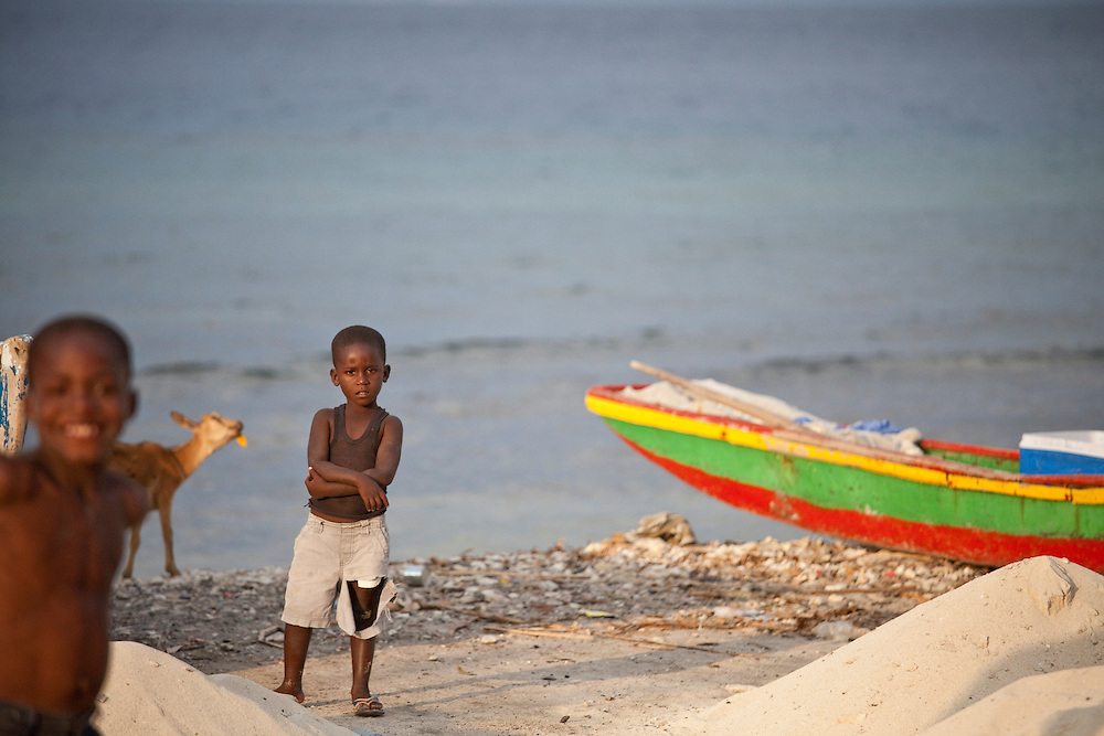 A boy on a beach surounded by colorful boats as the sun sets in Anse a Gaket, Ile de la Gonave, Haiti