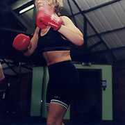 A woman wearing boxing gloves and sportswear in a gym