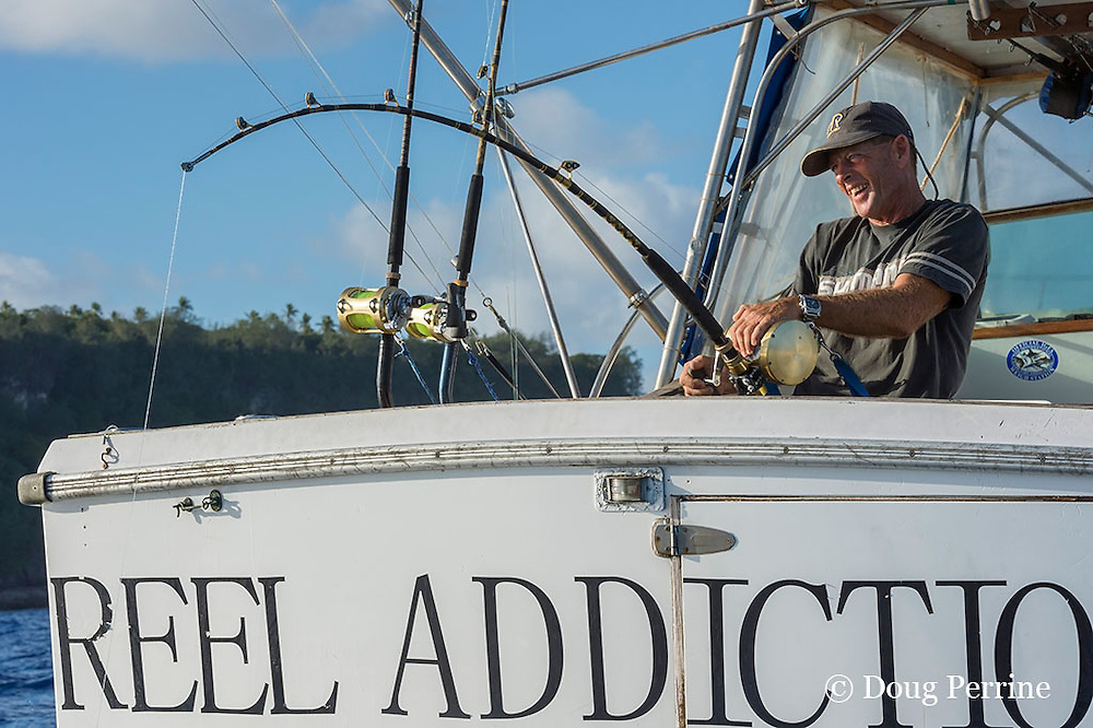 Captain Steve Campbell, fighting a fish aboard Reel Addiction, off Hunga Island, Vava'u, Kingdom of Tonga, South Pacific