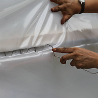"""Amanda Huels squeezes """"wiggle wire"""" into place to secure the plastic covering to the new greenhouse at Lawndale Elementary School."""