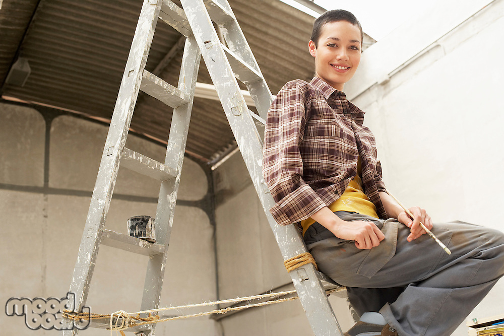 Female interior decorator sitting on ladder in work site portrait low angle view