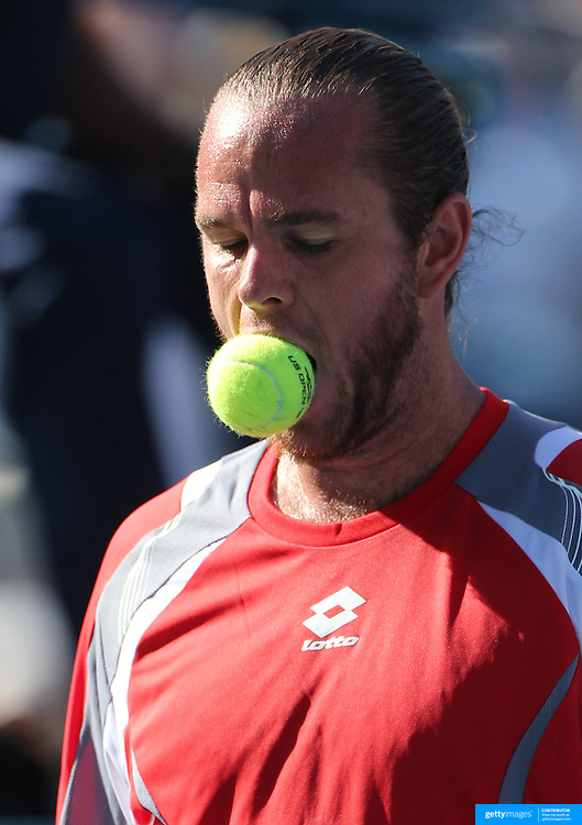 Xavier Malisse, Belgium, reacts by biting the ball after missing a shot against John Isner, USA, during the US Open Tennis Tournament, Flushing, New York. USA. 29th August 2012. Photo Tim Clayton