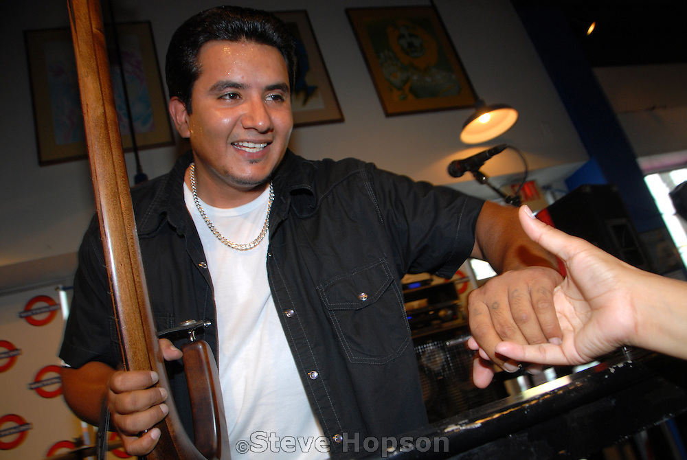 Jojo Garza of the band, Los Lonely Boys, shakes the hand of a fan at their appearance at Waterloo Records in Austin Texas, July 3 2008.  Los Lonely Boys are an American Grammy-winning musical rock band from San Angelo, Texas. They play Texican Rock n' Roll, combining elements of rock and roll, blues, soul, country, and Tejano. Their influences include Stevie Ray Vaughan, Santana, and Ritchie Valens.  The band consists of three brothers: Henry Garza, Jojo Garza, and Ringo Garza.