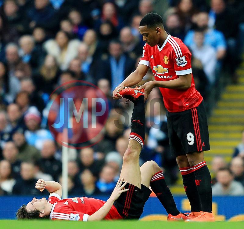 Anthony Martial of Manchester United treats Matteo Darmian's cramp - Mandatory byline: Matt McNulty/JMP - 20/03/2016 - FOOTBALL - Etihad Stadium - Manchester, England - Manchester City v Manchester United - Barclays Premier League