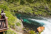 Hikers on viewing platform watching Fly fisherman casting into clear blue water below the falls in the natural spring water at Box Canyon State Park, Wendell, Idaho.