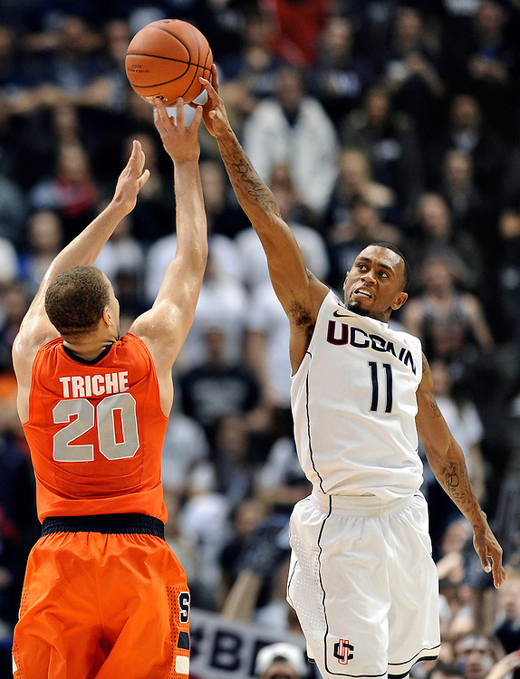 Connecticut's Ryan Boatright, right, blocks a shot-attempt by Syracuse's Brandon Triche in the final minutes of second half of an NCAA college basketball game in Hartford, Conn., Wednesday, Feb. 13, 2013. Connecticut won 66-58. (AP Photo/Jessica Hill)