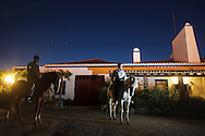 Two men riding horses at night at Casa Saramago in Telheiro village, near Reguengos de Monsaraz in the Alentejo region, Portugal.