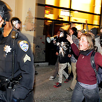 Protesters yell at Sgt. Dave Perry and other Santa Cruz Police officers on November 30 as they leave a former bank building occupied that day by 20-30 protesters. After a brief confrontation, the police left to regroup. The standoff ended three days later when the occupyers left on their own as police were massing to evict them forcibly.<br />Photo by Shmuel Thaler/Santa Cruz Sentinel