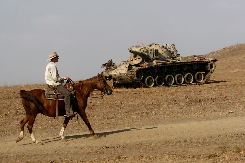 Yehuda Gilad 27 passing a trying tank during gathering of the cattle for veterinary checks in Moshav Yehonatan in the Golan height, Israel...Tuesday, October, 02, 2007..