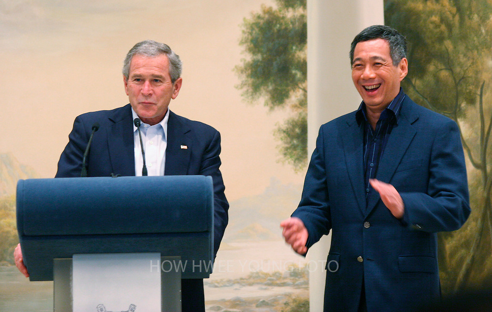 epa00863868 US President George W. Bush (L) and Singapore's Prime Minister Lee Hsien Loong shares a light moment during a dinner at the Istana in Singapore on Thursday 16 November 2006. Bush arrives in Singapore Thursday while enroute to attend the annual Asia-Pacific Economic Cooperation (APEC) summit in Vietnam.  EPA/HOW HWEE YOUNG
