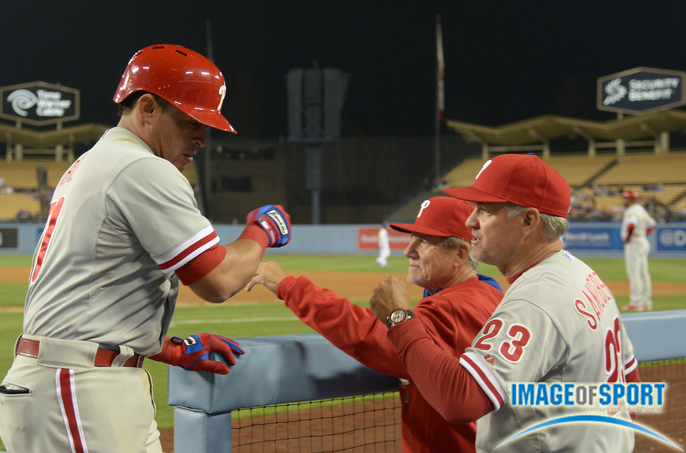 Apr 21, 2014; Los Angeles, CA, USA; Philadelphia Phillies catcher Carlos Ruiz (left) is greeted by bench coach Larry Bowa (center) and manager Ryne Sandberg after hitting a two-run home run in the ninth inning against the Los Angeles Dodgers at Dodger Stadium. The Phillies defeated the Dodgers 7-0.