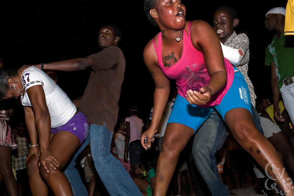 "Jamaican youths dance in the ""wine pon it"" style, a graphic simulation of sex that is common in Jamaican dance parties even amongst the youngest of party-goers, December 15, 2008 in the Trenchtown district of central Kingston. Hyper-sexuality amongst teenagers in Jamaica fuels a high teen pregnancy rate in the inner-city, and a continuing problem with children born out of wedlock that has broken down the traditional family structure. Critics point to this breakdown as a leading factor fueling inner city problems in Jamaica, including the high levels of violence and murder."