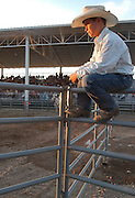 A junior bull rider, unable to compete because he had been kicked in the leg by a small steer the previous day, watches from the top of the arena fencing as the older riders compete.
