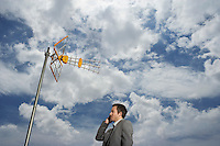 Business man using cell phone underneath satellite tower
