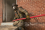 A firefighter holds onto a firehose at the entrance to a burning home.