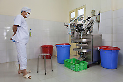 A processing unit worker of the National Institute of Nutrition observes a machine print labels for therapeutic food packets developed  jointly by NIN, IRD and UNICEF and processed at the University of Agriculture in Hanoi, Vietnam, Southeast Asia