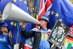 © Licensed to London News Pictures. 01/05/2019. London, UK. Anti-Brexit campaigner Steve Bray stands outside Parliament with a giant megaphone and an anti Theresa May poster. Photo credit: Dinendra Haria/LNP