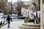An Azeri woman extends the clothes on the street near downtown. Azeri GDP grew 41.7% in the first quarter of 2007, possibly the highest of any nation worldwide, as the country economy completed its post-Soviet transition into a major oil based economy.<br /> Baku was awarded the right to host of the first European Games, a multi-sport event.