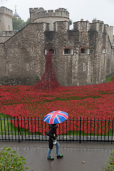 © Licensed to London News Pictures. 26/08/2014. London, UK. A woman with an umbrella passes the poppy moat at the Tower of London. Heavy rain and cold weather are forecast for the rest of the day. Photo credit : Vickie Flores/LNP