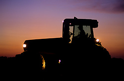 Stock photo of the silhouette of a man driving a tractor at sunset
