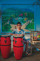 A young boy named Eduardo practices drums in Santiago de Los Caballeros in the Dominican Republic. Behind Eduardo hangs a painting by the Dominican artist Ricardo Toribio who paints scenes celebrating life on the island, especially that of the native Tainos who European colonialists enslaved alongside African slaves imported in the 15th century. The country, and its neighbor Haiti, still struggle with racism and ethnic divisions, but art celebrating the lives of the descendants of slaves has found a new audience and acclaim.