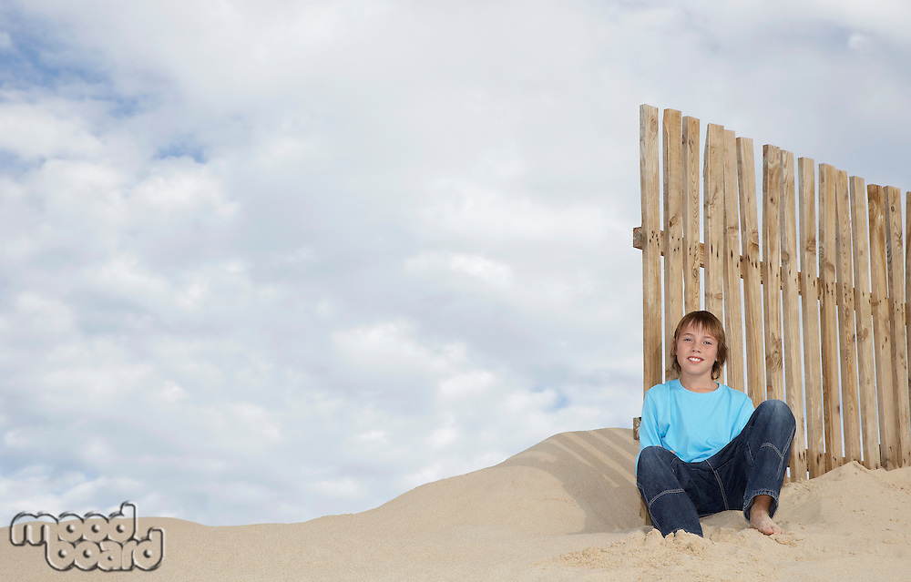 Boy (10-12) sitting against wooden fence on sand dune portrait
