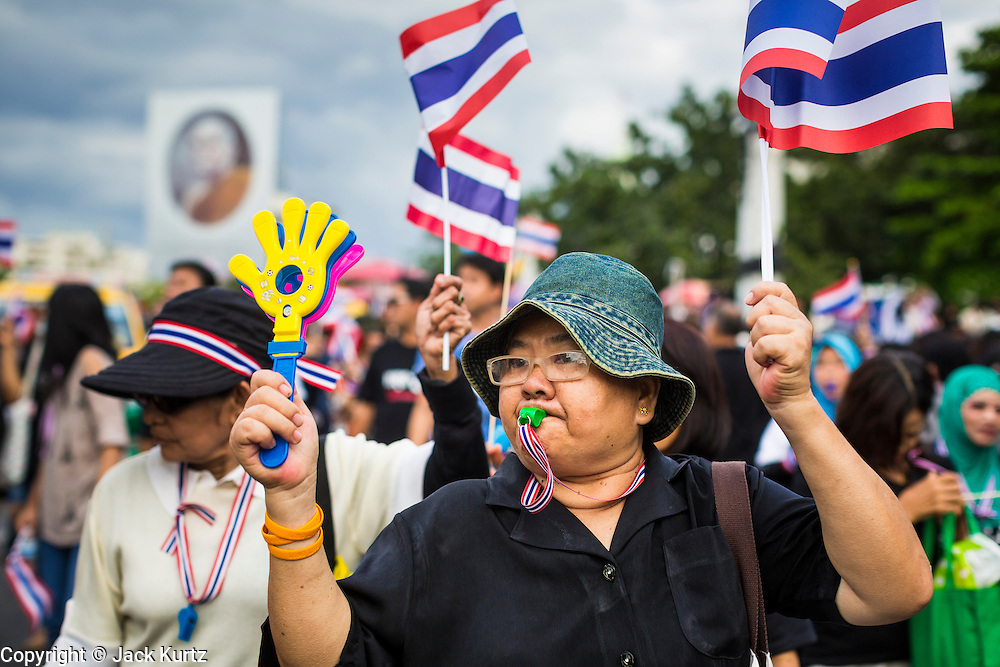 "15 NOVEMBER 2013 - BANGKOK, THAILAND:  A woman waves Thai flags and blows a whistle during an anti-government protest in Bangkok. Tens of thousands of Thais packed the area around Democracy Monument in the old part of Bangkok Friday night to protest against efforts by the ruling Pheu Thai party to pass an amnesty bill that could lead to the return of former Prime Minister Thaksin Shinawatra. Protest leader and former Deputy Prime Minister Suthep Thaugsuban announced an all-out drive to eradicate the ""Thaksin regime."" The protest Friday was the biggest since the amnesty bill issue percolated back into the public consciousness. The anti-government protesters have vowed to continue their protests even though the Thai Senate voted down the bill, thus killing it for at least six months.    PHOTO BY JACK KURTZ"