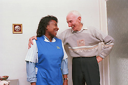 Carer and elderly man standing together laughing,