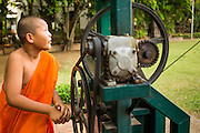 10 APRIL 2013 - CHIANG MAI, CHIANG MAI, THAILAND:  A novice (student monk) operates a winch that sends Songkran offerings to the top of the chedi at Wat Phra Singh in Chiang Mai. Songkran is celebrated in Thailand as the traditional New Year's Day from 13 to 16 April. Songkran is in the hottest time of the year in Thailand, at the end of the dry season and provides an excuse for people to cool off in friendly water fights that take place throughout the country. The traditional Thai New Year has been a national holiday since 1940, when Thailand moved the first day of the year to January 1. The first day of the holiday period is generally the most devout and many people go to temples to make merit and offer prayers for the new year.    PHOTO BY JACK KURTZ