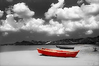 A red fisherman boat on a black and white beach