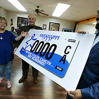 Thomas Wells | BUY AT PHOTOS.DJOURNAL.COM<br /> Aaron Washington, right, and Dr. Sam Pace hold up an approved mock car tag as designer Lelsie Geoghegan, left, shows what when into designing a car tag for Colon Cancer survivors.