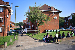 © Licensed to London News Pictures. 15/09/2016. London, UK. Grieving relatives and friends sit at the entrance to a flat which was the scene of a double shooting in a block of flats in East Finchley. Police were called by London Ambulance Service at 06:25hrs this morning to reports of two people injured at an address in north London. A man and a woman were found with gunshot injuries. Both were pronounced dead at the scene. Photo credit: Ben Cawthra/LNP