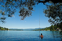 Gabe Eifler, 14, grips onto the rope swing at Hayden Lake while he waits to toss the rope to someone else to jump into the water Thursday.