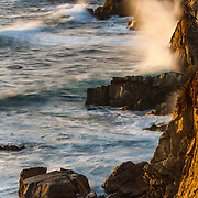 The incoming tide surrounds coastal boulders along the coast of Big Sur near Monterey, California.