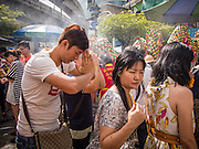 17 AUGUST 2013 - BANGKOK, THAILAND:    A man prays at Erawan Shrine in Bangkok while a dragon dance troupe finishes its performance. The Chinese Dragon Dance began during the Han Dynasty which lasted from 206 BC to 24 AD. In those ancient days it was performed by the people of China specifically to please their ancestors and to insure sufficient rain for a plentiful crop. In this way they hoped to protect against hunger and sickness. Over time the Dragon Dance became a central feature in Chinese celebrations with different colors symbolizing different characteristics or desired features; red for excitement, green for a good harvest, yellow for a solemn empire and gold or silver for prosperity. The Dragon Dance is a well-choreographed event whose difficulty is dependent upon the performers' skill. The length of the dragon indicates just how much luck it will bring in the coming year, but a longer dragon requires more performers with great skill as an error by one can ruin the entire performance. The dragon is typically between 82 and 229 feet long. The head along can weigh as much as 31 pounds. Both strength and skill are both required in performing the Chinese Dragon Dance.        PHOTO BY JACK KURTZ