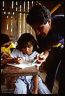 Teacher checks girl's work at jungle school for rubber tappers' kids on Seringal Cachoeira, Acre Brazil