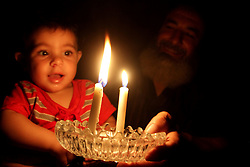 28.07.2015, Rafah, PSE, Stromausfall in Rafah, im Bild Palästinenser im Kerzenschein während einen Stromausfall // A Palestinian man sits with his grandson as he uses a candle light during a power cut. Independent Commission for Human Rights warned Saturday of the aggravated humanitarian situation in Gaza due to continued electricity outage after the Gaza's sole power plant stopped running, which make problems with water supply because many of the area's water pumps also rely on that power plant, Palestine on 2015/07/28. EXPA Pictures © 2015, PhotoCredit: EXPA/ APAimages/ Abed Rahim Khatib<br /> <br /> *****ATTENTION - for AUT, GER, SUI, ITA, POL, CRO, SRB only*****