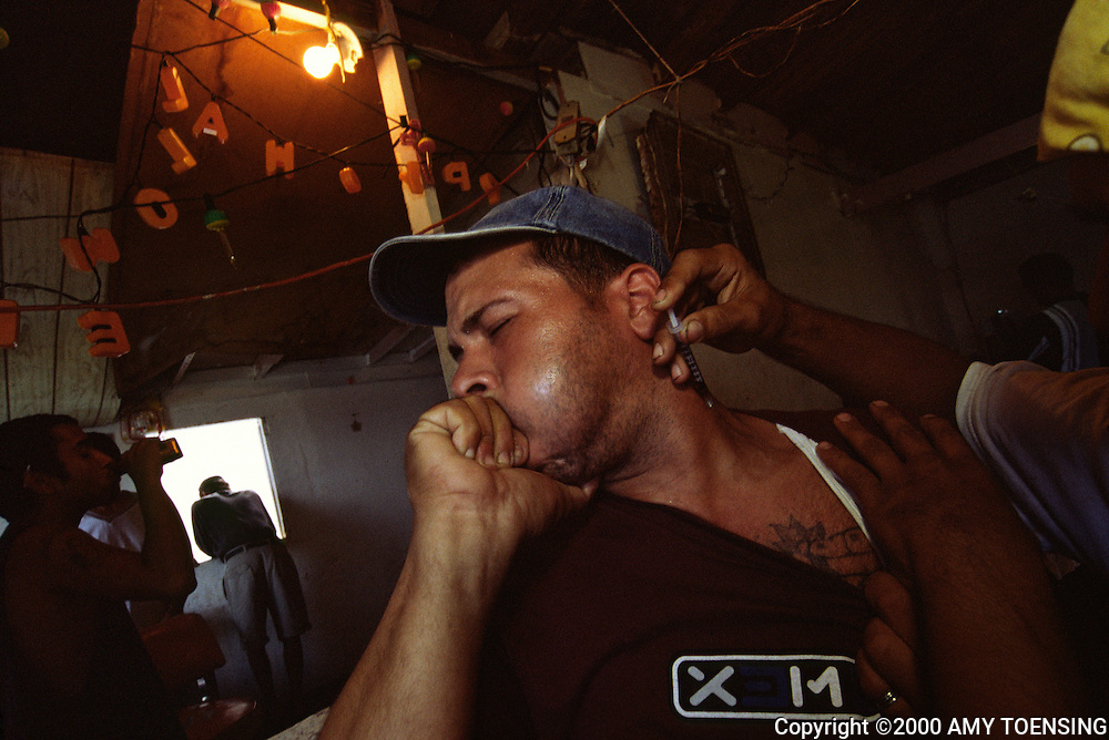 OLD SAN JUAN, PR - November 14: A man receives a heroin injection in a shooting gallery in the neighborhood of La Perla, November 14, 2001 in Old San Juan, Puerto Rico. Puerto Rico was an outpost of Spanish colonialism for 400 years, until the United States took possession in 1898. Today Puerto Rico's Spanish-speaking culture reflects its history - a mix of African slaves, Spanish settlers, and Taino Indians. Puerto Ricans fight in the U.S. armed forces but are not entitled to vote in presidential elections. They passionately debate their relationship with the U.S. with about half the island wanting to become the 51st state and the other half wanting to remain a U.S. commonwealth. A small percentage feel the island should be an independent country. While locals grapple with the evils of a burgeoning drug trade and unchecked development, drumbeats still drive the rhythms of African-inspired bomba music. (Photo By Amy Toensing) _________________________________<br />