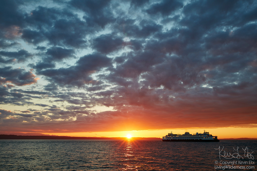 A Washington State Ferry crosses Puget Sound from Edmonds, Washington, as the sun sets under dark, cloudy skies.