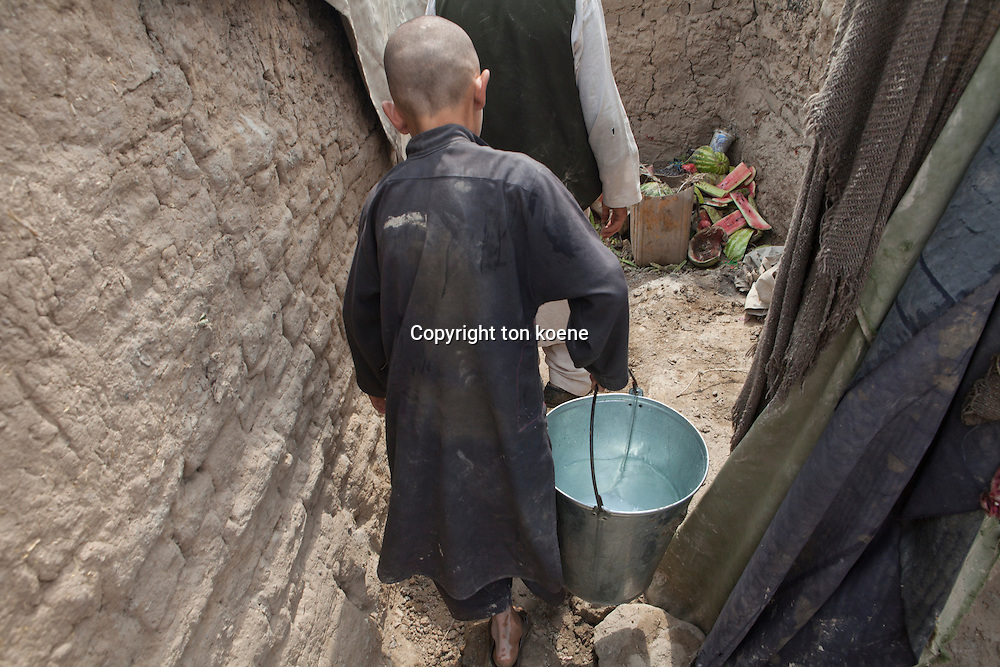 Afghan refugee child fetching water from the well