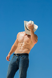 Shirtless muscular cowboy against a blue sky