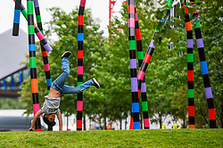 "© Licensed to London News Pictures. 16/07/2020. LONDON, UK.  Zeph, aged 5, performs cartwheels at the unveiling of ""My World and Your World"", by major contemporary London-based, Irish artist Eva Rothschild.  The new 16m high public sculpture in Lewis Cubitt Park in King's Cross resembles a lightning bolt, painted in black, purple, pink, orange, green and red stripes.  The coronavirus lockdown caused the April 2020 launch to be postponed, but the unveiling has been able to go ahead now that certain lockdown restrictions have been eased by the UK government. (Permission granted). Photo credit: Stephen Chung/LNP"