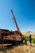 Two young men examine an abandoned oil drilling rig along Smugglers Road atop Santa Cruz Island, Channel Islands National Park, California, USA.
