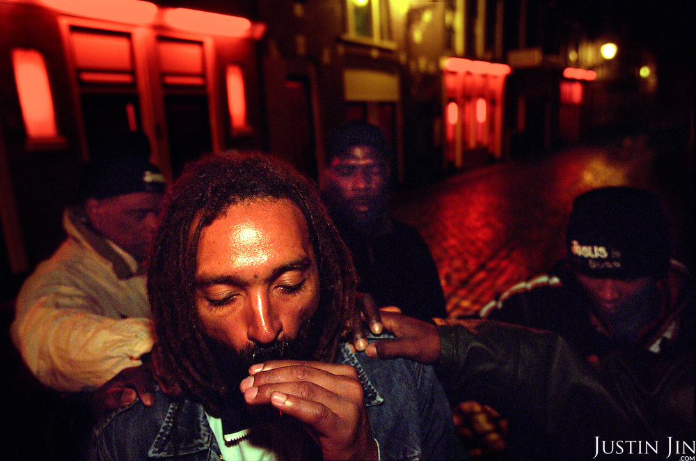 Evangelists pray for a crack addict in Amsterdam's Red-Light district. The evangelists are former addicts themselves...Victory Outreach, a controversial church started in Los Angeles in 1967, is spreading to Europe via the Netherlands. It builds its membership among junkies, prostitutes and criminals. ..Photo taken in the Netherlands in 2002. The picture is part of a photo and text documentary by Justin Jin. For more information, email justin@justinjin.com