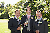 Three men in garden wearing full suits holding wineglasses portrait