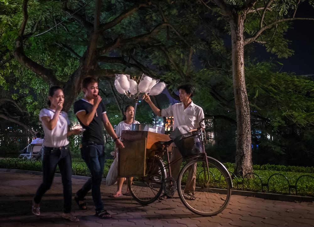 HANOI, VIETNAM - CIRCA SEPTEMBER 2014:  People walking at the Hoan Kiem Lake at night in Hanoi, Vietnam.